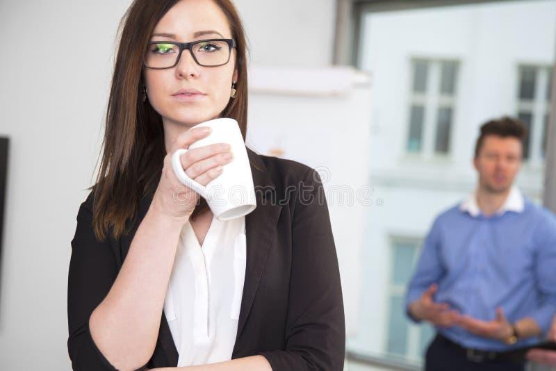 拿着咖啡杯的女实业家,当站立在Bac中时的同事 免版税库存照片