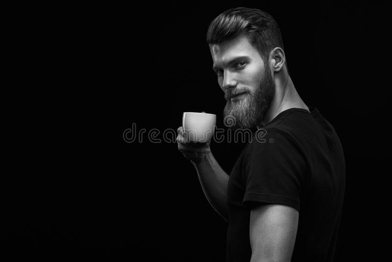 拿着咖啡杯的微笑的行家有胡子的人 免版税库存图片