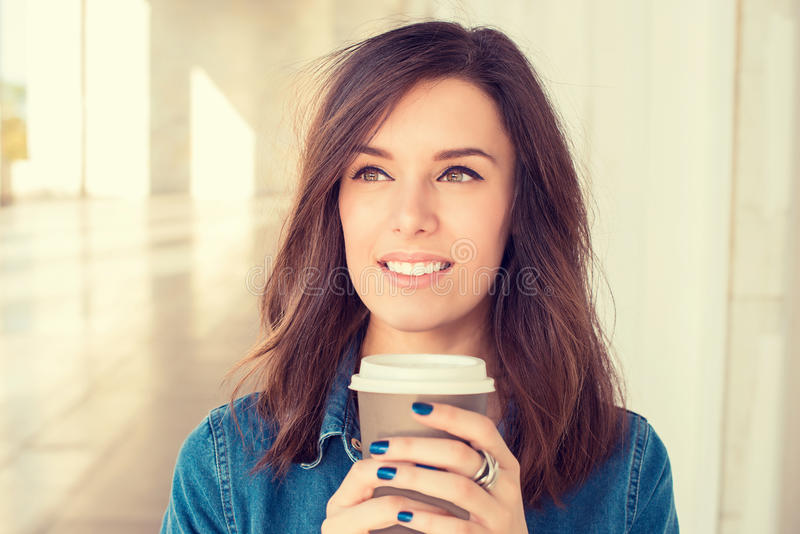 拿着咖啡杯的快乐的妇女户外 免版税库存图片