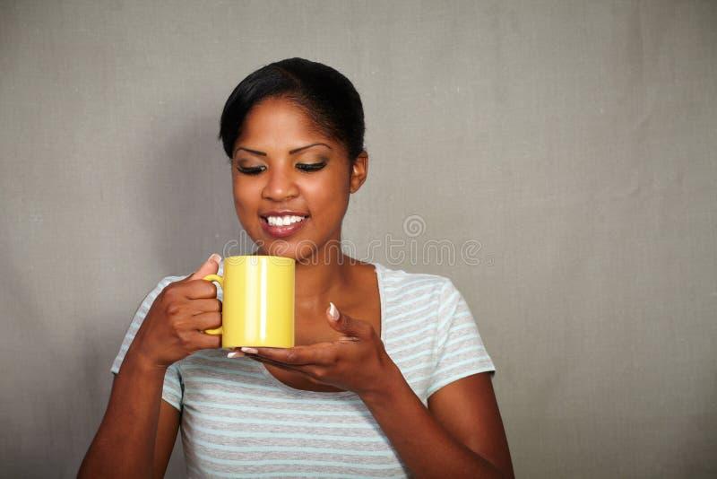 拿着咖啡杯的愉快的女孩,当微笑时 免版税图库摄影