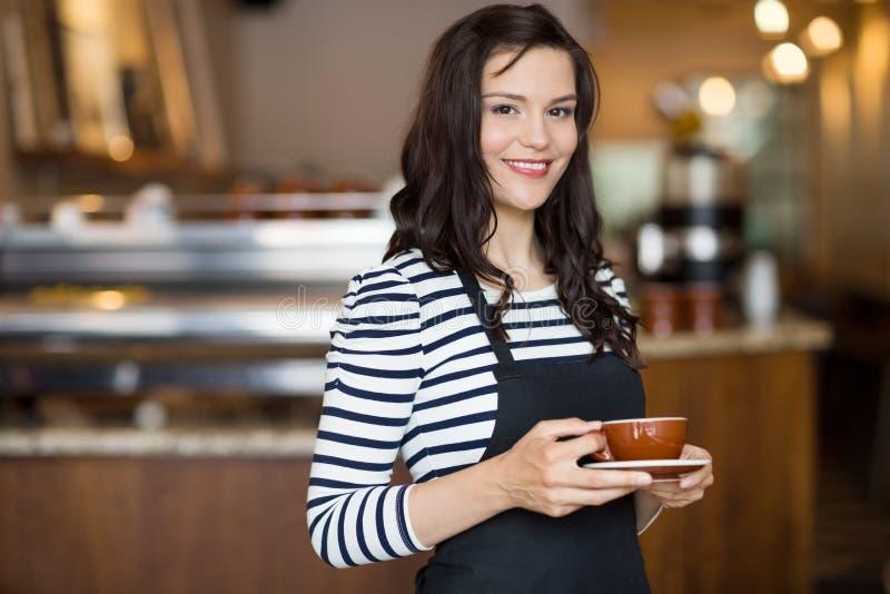 拿着咖啡杯的美丽的女服务员在自助食堂 库存照片