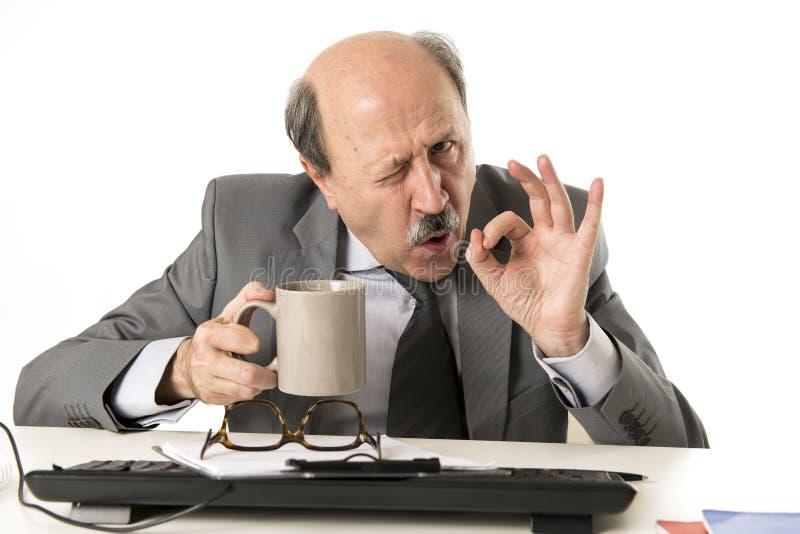 拿着咖啡杯drinkin的友好的60s秃头资深商人 库存图片