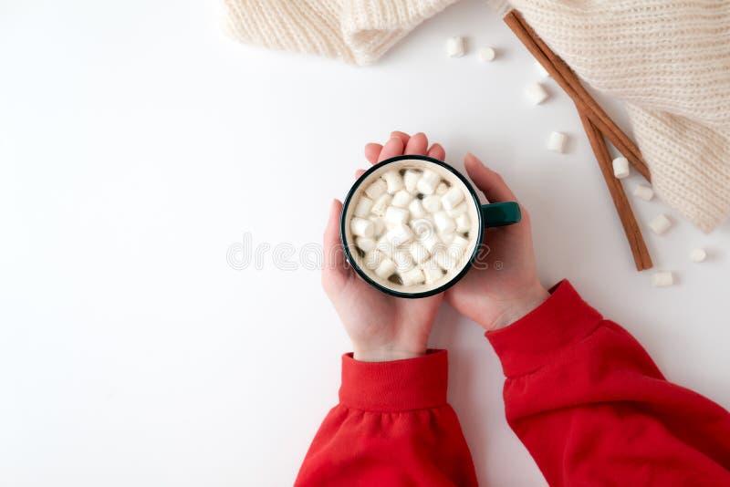 拿着咖啡的女性手用在白色背景的蛋白软糖 红色毛线衣的女孩有咖啡的 节假日 免版税图库摄影