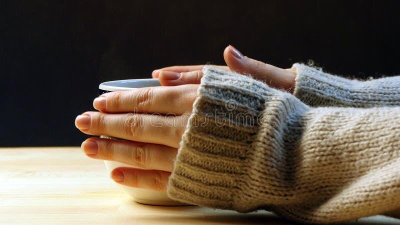 拿着咖啡的妇女,温暖她的手 免版税库存照片