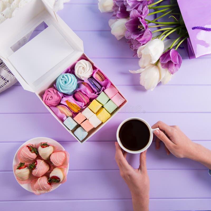 拿着咖啡的年轻女性手在五颜六色的蛋白软糖和蛋白杏仁饼干附近在箱子,紫色和白色郁金香花束设置了和 图库摄影