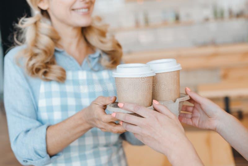 拿着咖啡的特写镜头部份观点的女服务员和买家进来在纸 库存图片