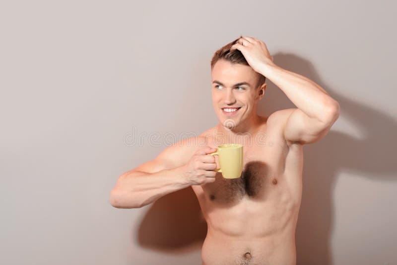 拿着咖啡的英俊的露胸部的人 免版税库存图片