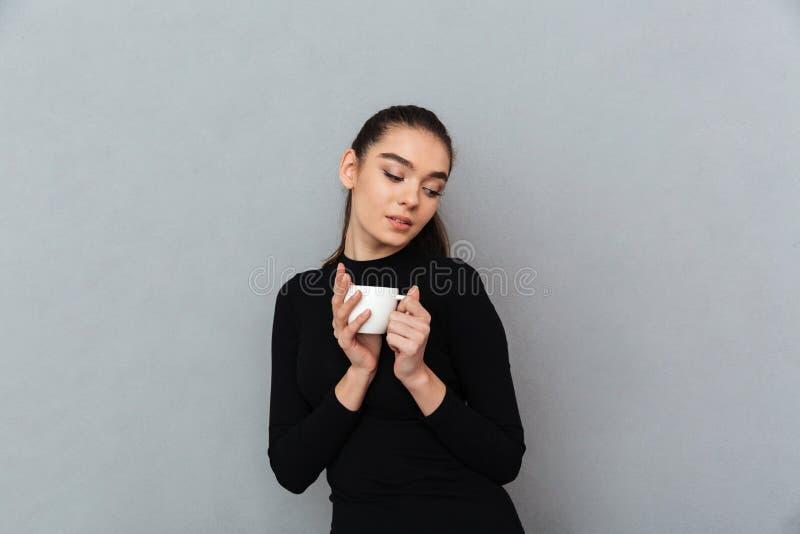 拿着咖啡的黑衣裳的喜悦的深色的妇女 免版税库存图片