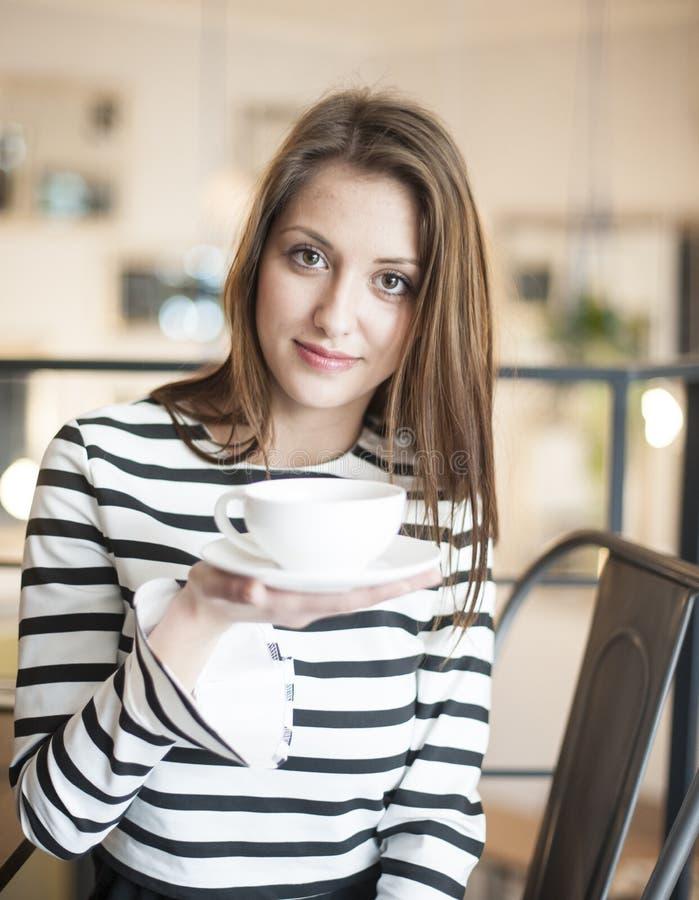 拿着咖啡茶杯的少妇画象在咖啡馆 免版税库存图片