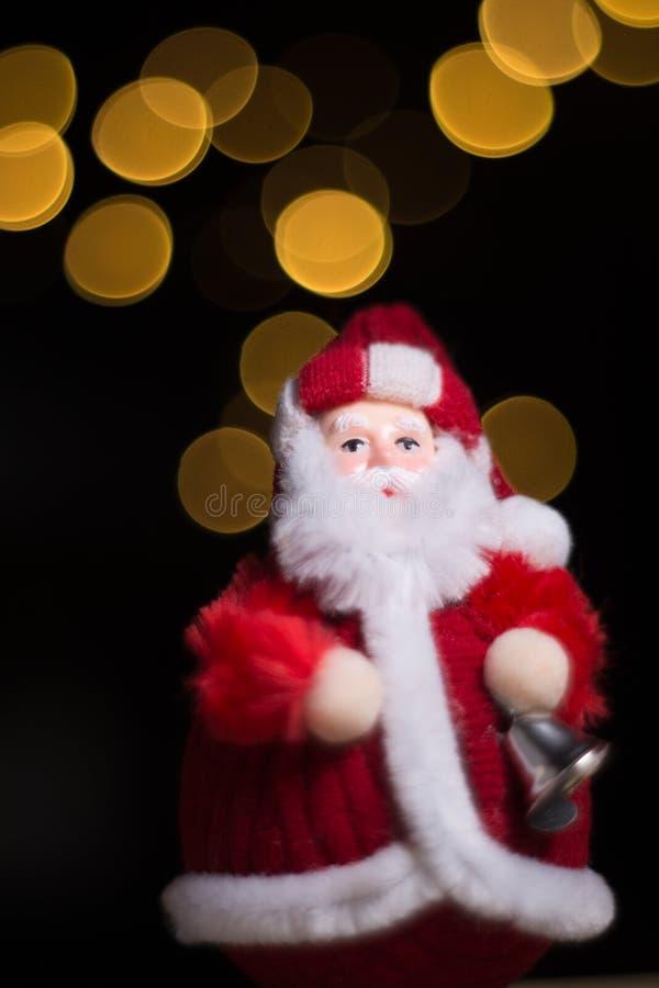 拿着响铃,圣诞节题材,黑背景的圣诞老人与 免版税库存图片