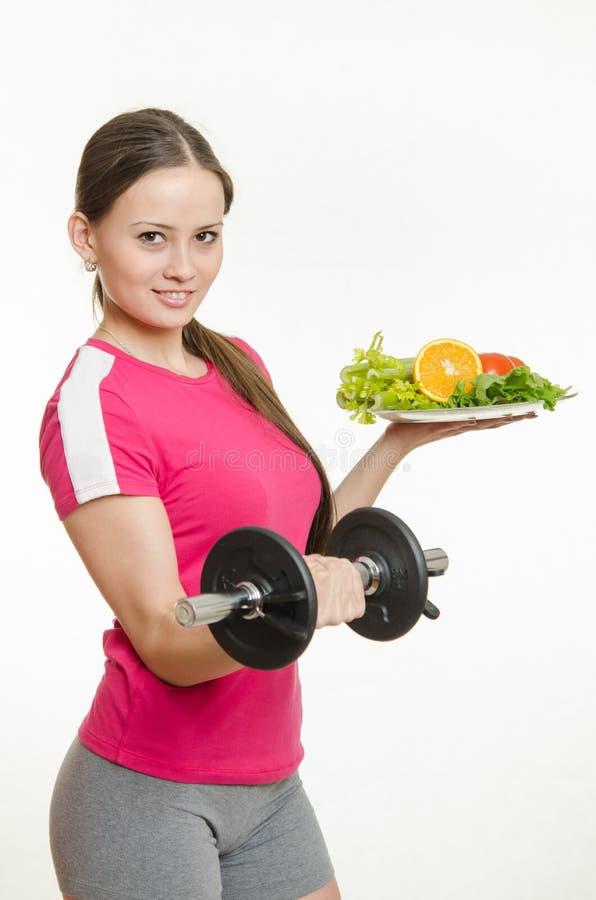 拿着哑铃和一碗果子的女运动员 免版税库存照片