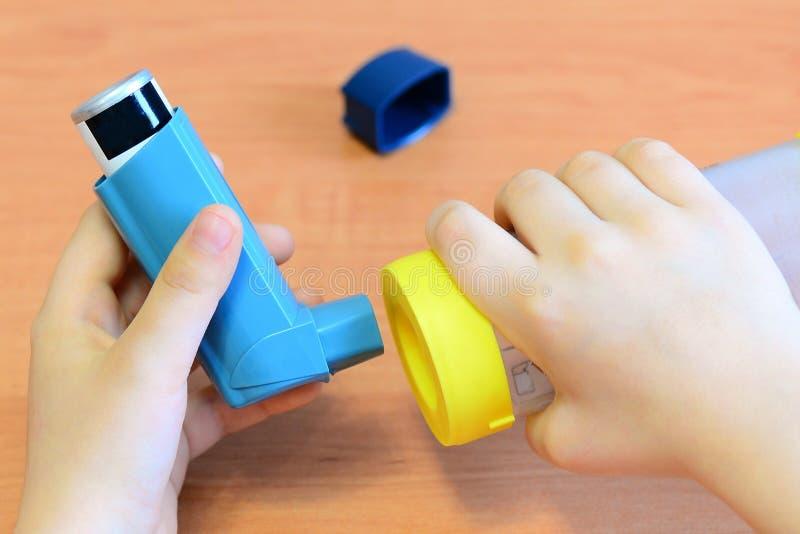 拿着哮喘吸入器和间隔号在他的手上的小孩子 哮喘间隔号和湿剂吸入器 免版税库存图片