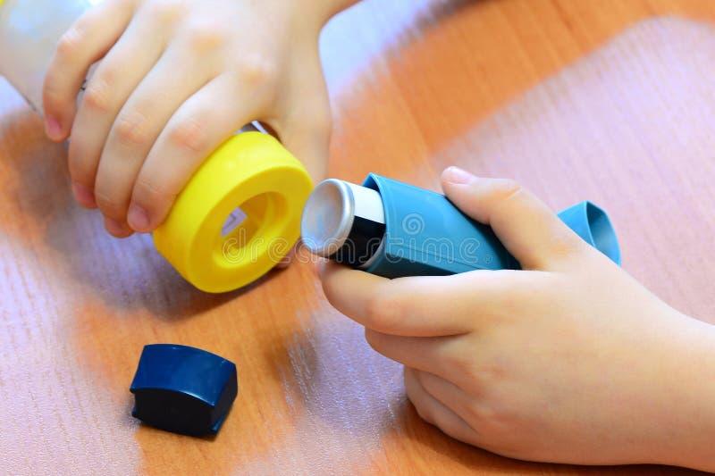 拿着哮喘吸入器和间隔号在他的手上的小孩子 疗程和医疗设备 免版税库存图片