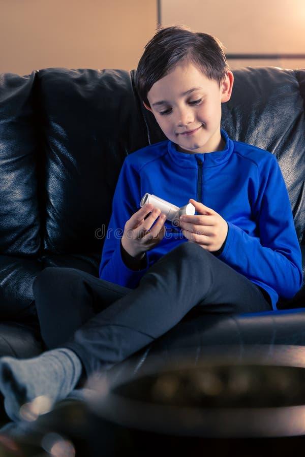 拿着哮喘吸入器的男孩 免版税图库摄影
