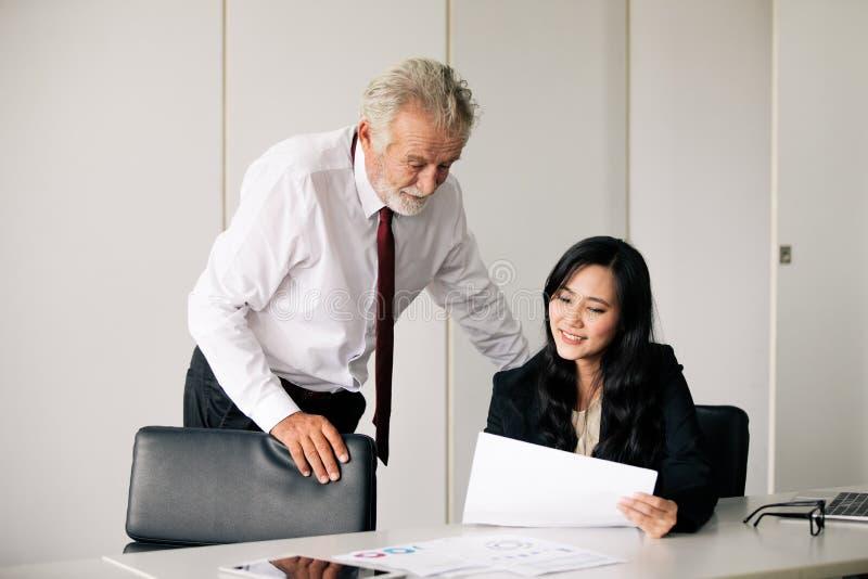拿着商务伙伴的商人文件谈论和分享想法在会议和女商人微笑愉快为 免版税库存照片