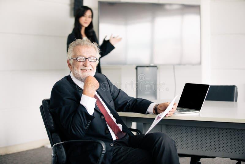 拿着商务伙伴的商人文件谈论和分享想法在会议和女商人微笑愉快为 免版税库存图片