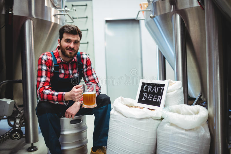 拿着啤酒杯的制造商在啤酒厂 图库摄影
