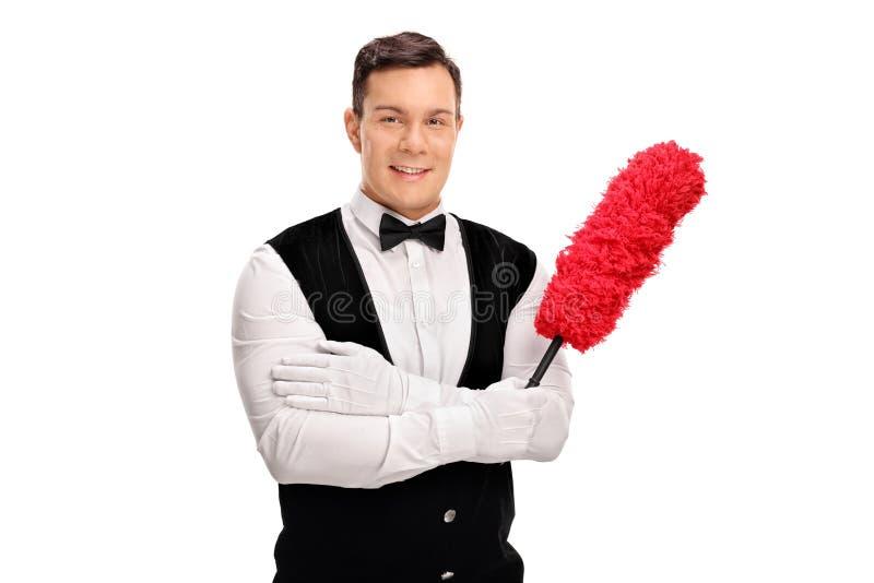 拿着喷粉器的年轻快乐的男管家 免版税库存照片