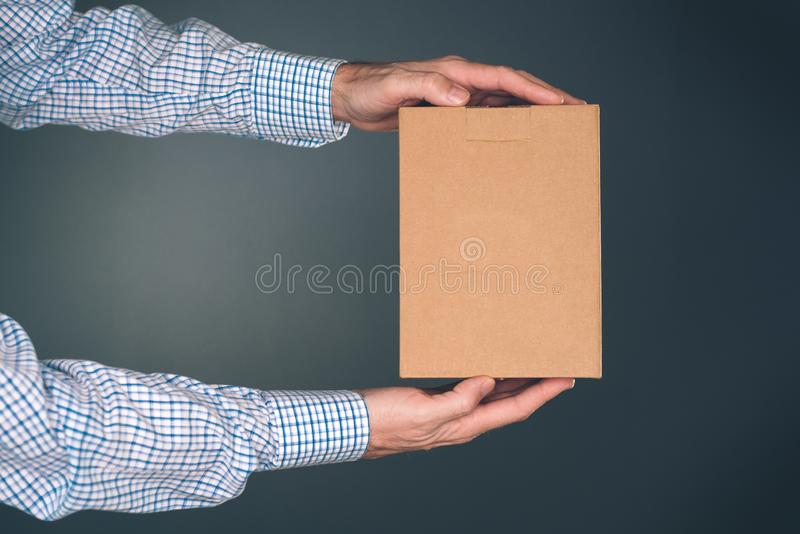 拿着嘲笑的人纸板箱包裹设计 库存图片