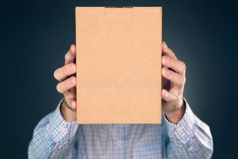 拿着嘲笑的人纸板箱包裹设计 库存照片
