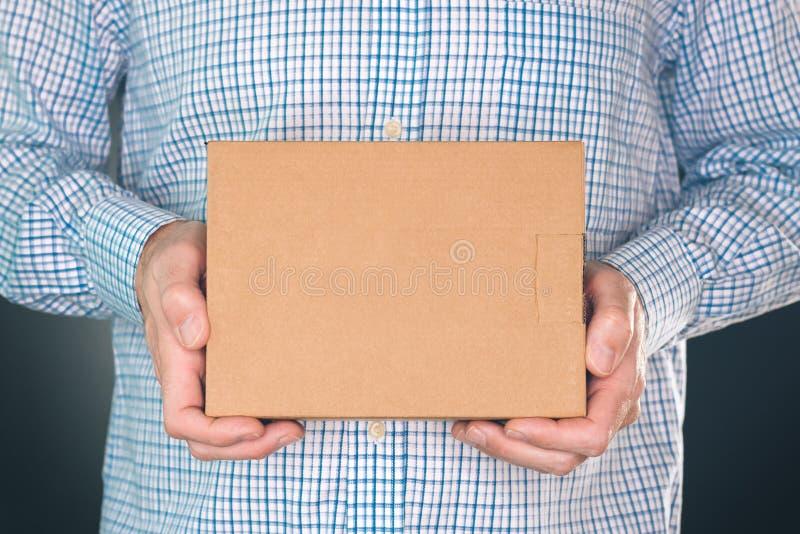 拿着嘲笑的人纸板箱包裹设计 免版税库存图片