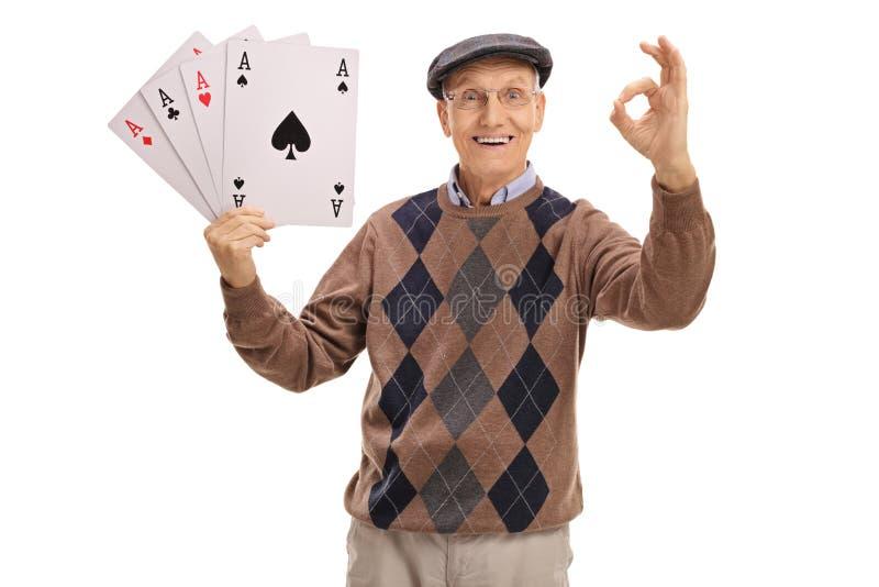 拿着四一点和做一个好标志的快乐的前辈 免版税库存照片
