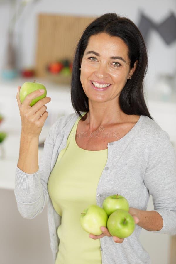 拿着四个苹果的可爱的成熟妇女 免版税库存照片