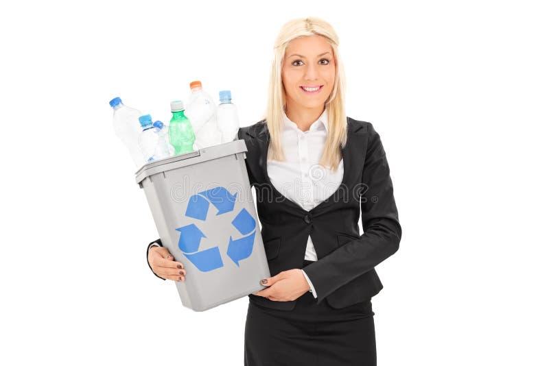 拿着回收站的妇女有很多塑料瓶 免版税库存照片