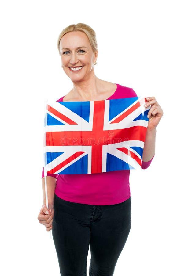 拿着国旗的快乐的女性支持者 库存图片
