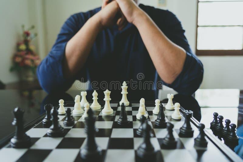 拿着国王Chess的商人在棋枰被安置 使用作为背景企业概念和战略概念与拷贝 免版税图库摄影