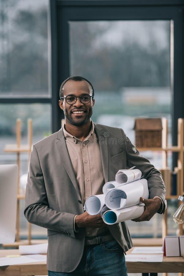 拿着图纸的快乐的非裔美国人的建筑师 免版税库存照片