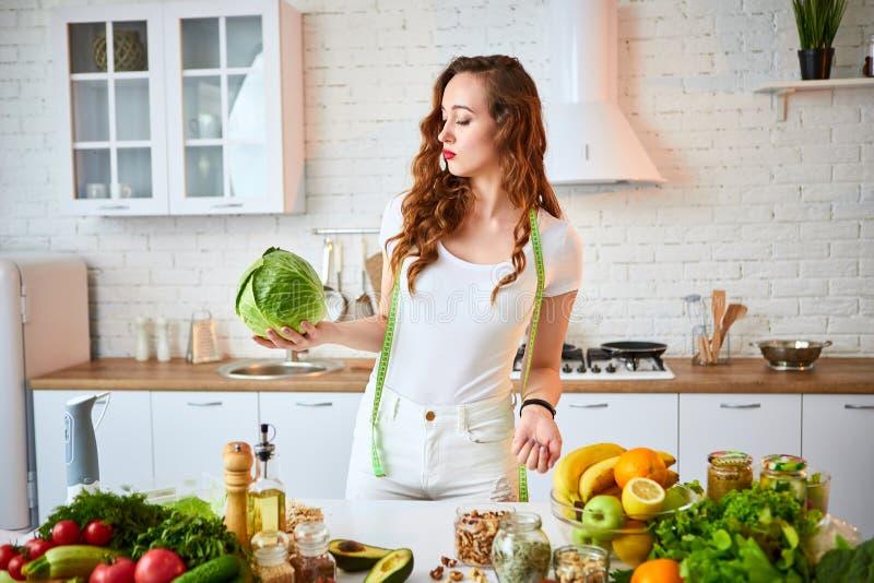拿着圆白菜的年轻愉快的妇女在有绿色新鲜的成份的美丽的厨房里户内 健康食品和节食的概念 免版税图库摄影