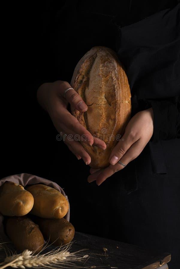 拿着土气有机面包在手上-农村面包店的贝克妇女 自然光,喜怒无常的静物画 库存照片