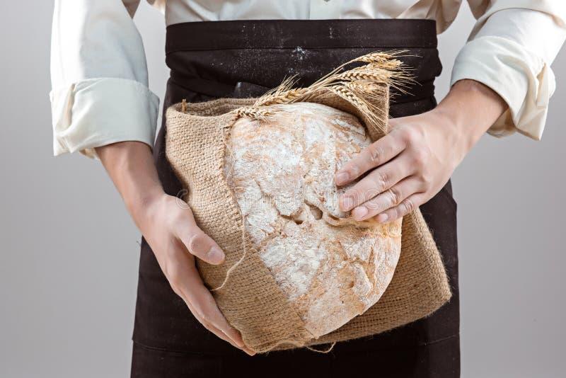 拿着土气有机面包的贝克人在手上 免版税库存图片