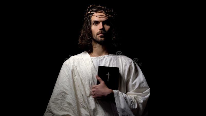 拿着圣经的铁海棠的人直接地看,耶稣在十字架上钉死前 免版税库存照片