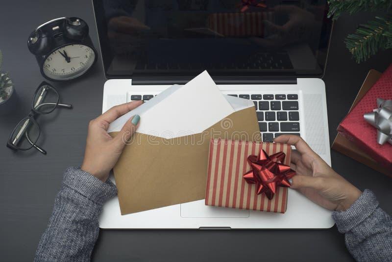 拿着圣诞卡和礼物盒在书桌上的女商人手 免版税库存图片