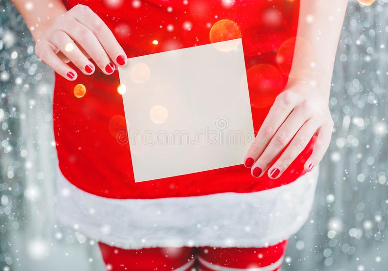 拿着圣诞快乐卡片或信件的女性手对圣诞老人 Xmas和新年题材 免版税库存图片