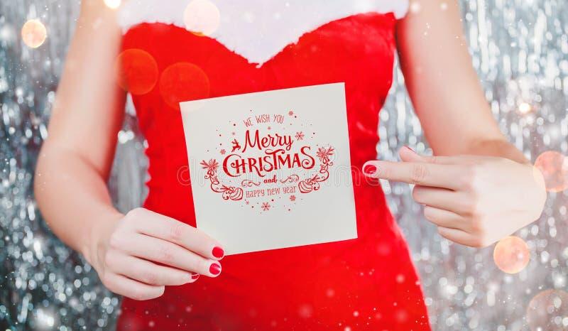 拿着圣诞快乐卡片或信件的女性手对圣诞老人 Xmas和新年题材 库存图片