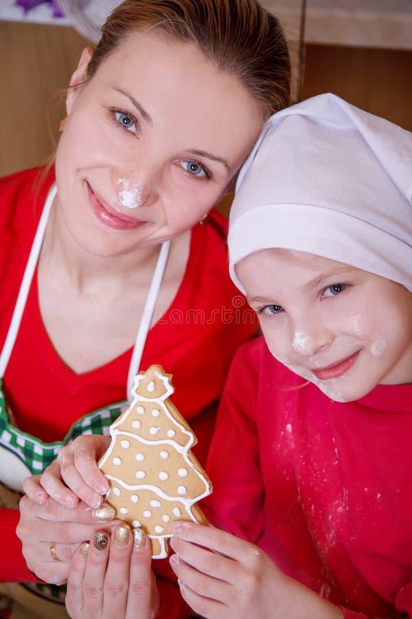 拿着圣诞树饼干的母亲和女儿 免版税库存图片