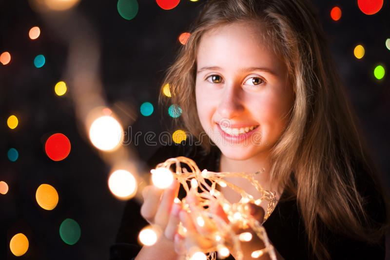 拿着圣诞灯的美丽的十几岁的女孩 图库摄影