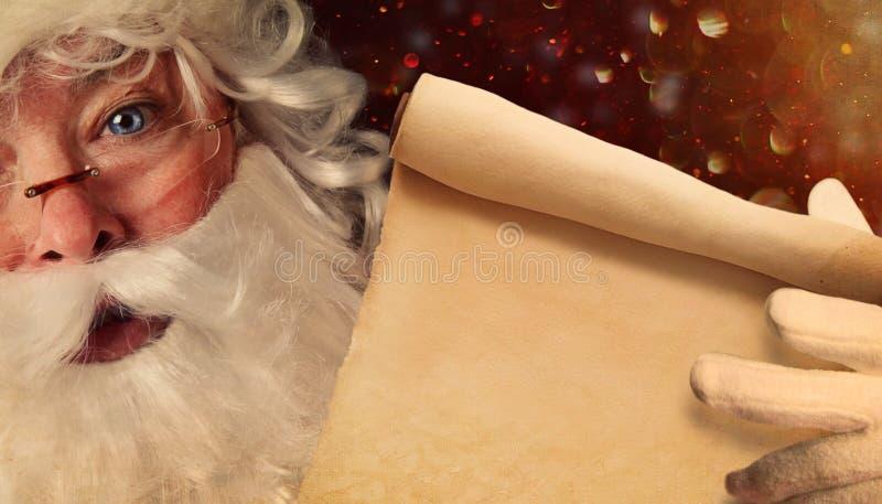 拿着圣诞老人名单的圣诞老人特写镜头 免版税库存照片