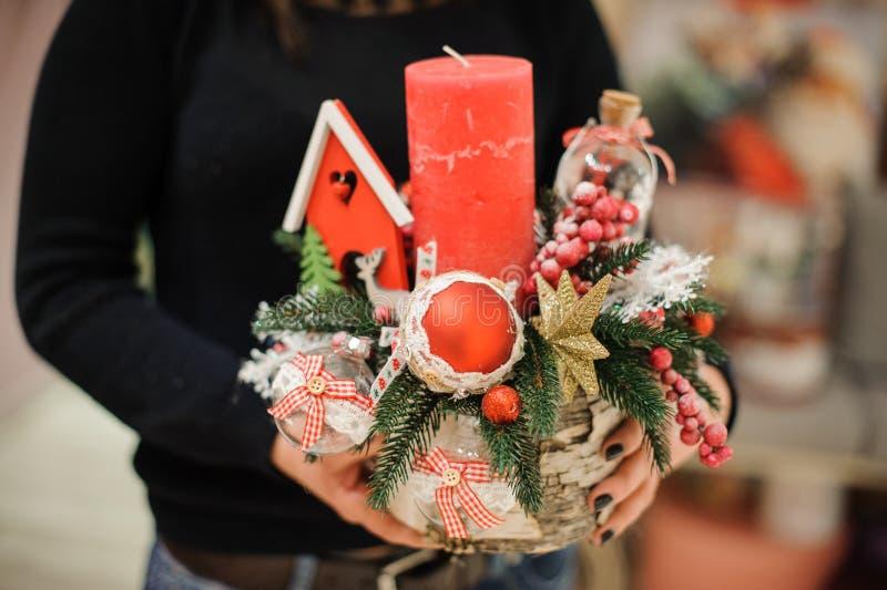 拿着圣诞节构成的妇女由杉树制成、五颜六色的玻璃球和玩具房子、蜡烛、星和莓果在花瓶 免版税库存图片