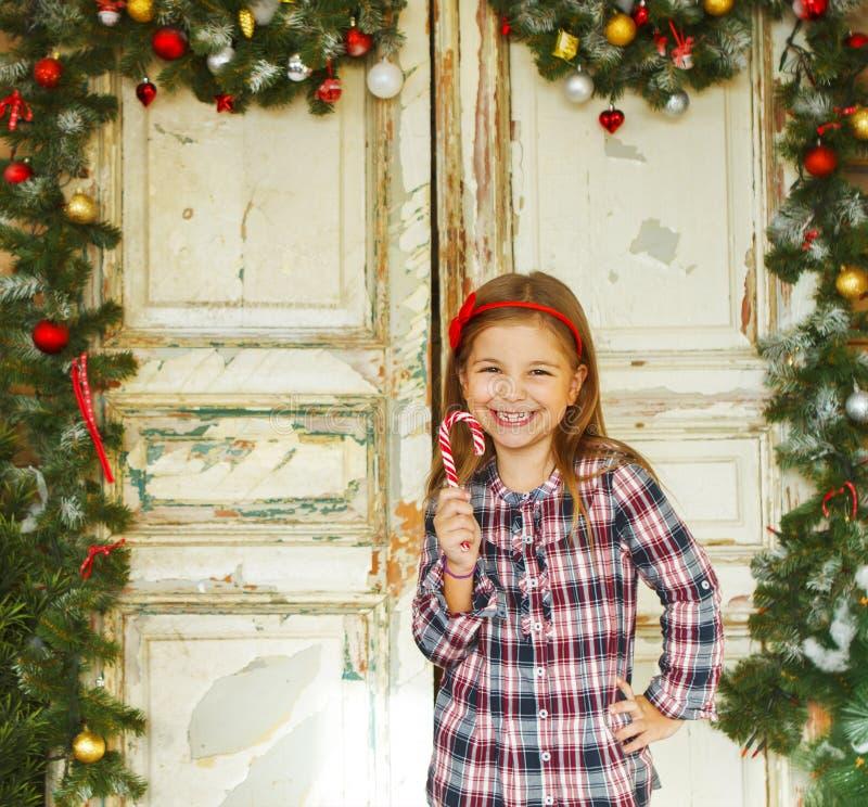 拿着圣诞节棒棒糖的愉快的小女孩 免版税图库摄影