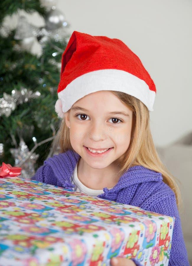 拿着圣诞节礼物的圣诞老人帽子的微笑的女孩 免版税库存照片