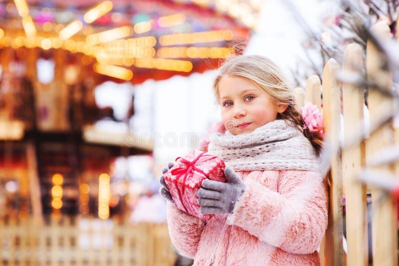 拿着圣诞节礼物的愉快的儿童女孩室外在步行在多雪的冬天城市 免版税库存图片
