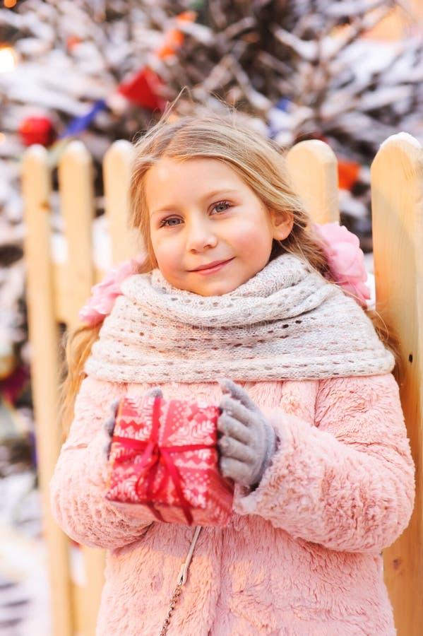 拿着圣诞节礼物的愉快的儿童女孩室外在步行在多雪的冬天城市 库存照片
