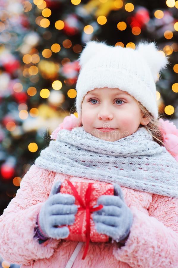 拿着圣诞节礼物的愉快的儿童女孩室外在步行在新年假日装饰的多雪的冬天城市 免版税图库摄影