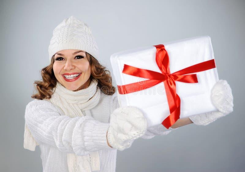 拿着圣诞节礼物的白色帽子的美丽的少妇 免版税库存照片