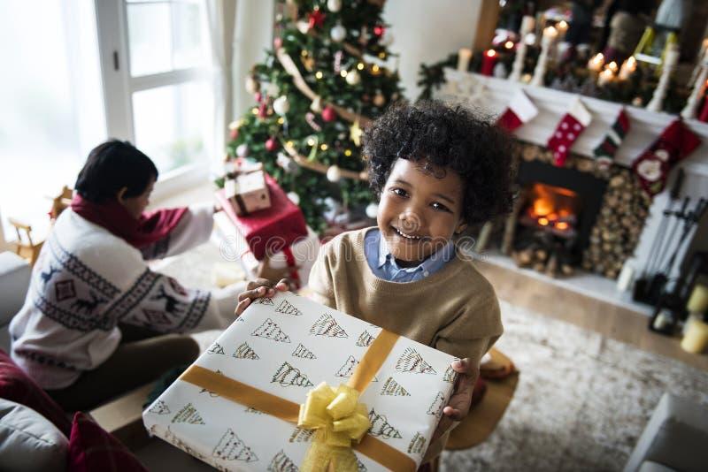 拿着圣诞节礼物的非洲孩子 免版税库存照片