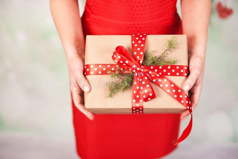 拿着圣诞节礼物盒的妇女的手 免版税库存照片